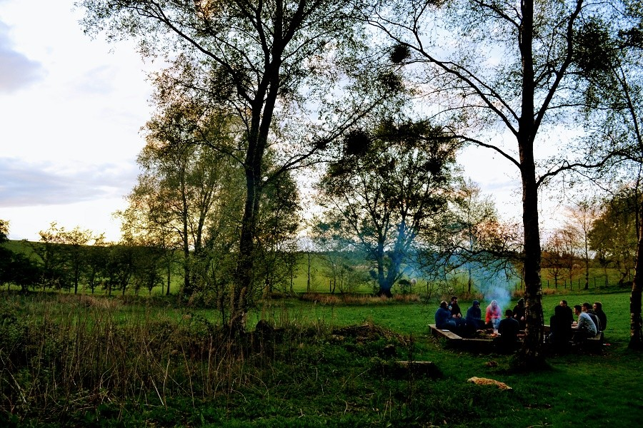 Corporate group enjoy a barbecue and camp fire near Carlisle, Cumbria